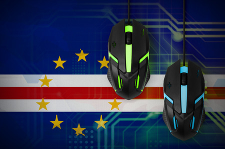 Cabo verde flag  and two modern computer mice with backlight. The concept of online cooperative games. Cyber sport team