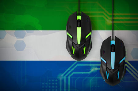 Sierra Leone flag  and two modern computer mice with backlight. The concept of online cooperative games. Cyber sport team