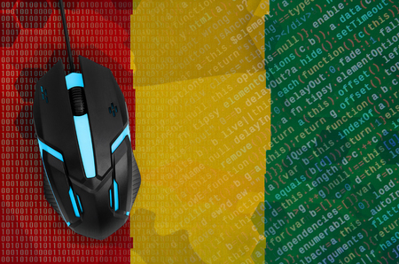 Guinea flag  and modern backlit computer mouse. The concept of digital threat, illegal actions on the Internet