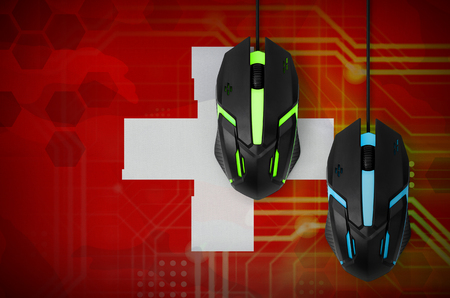 Switzerland flag and two modern computer mice with backlight. The concept of online cooperative games. Cyber sport team