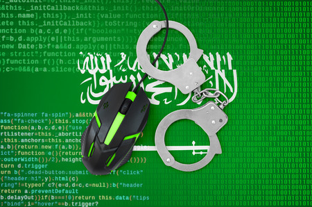 Saudi Arabia flag  and handcuffed modern backlit computer mouse. Creative concept of combating computer crime, hackers and piracy