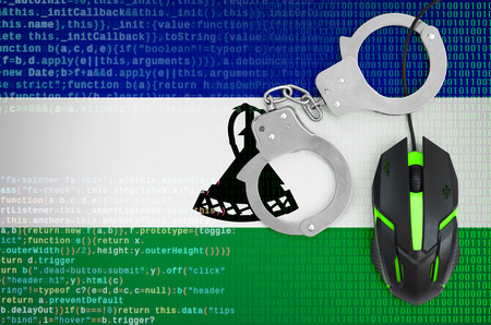 Lesotho flag  and handcuffed modern backlit computer mouse. Creative concept of combating computer crime, hackers and piracy Фото со стока