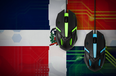 Dominican Republic flag  and two modern computer mice with backlight. The concept of online cooperative games. Cyber sport team