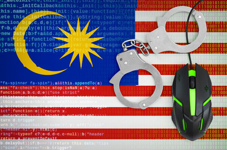 Malaysia flag  and handcuffed modern backlit computer mouse. Creative concept of combating computer crime, hackers and piracy