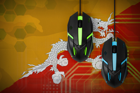Bhutan flag  and two modern computer mice with backlight. The concept of online cooperative games. Cyber sport team