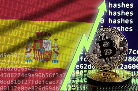 Spain flag and rising green arrow on bitcoin mining screen and two physical golden bitcoins. Concept of high conversion in cryptocurrency mining