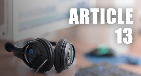 Article 13 inscription and headphones on the wooden desktop. European copyright directive including article 13 is approved by european parliament