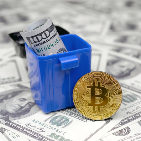 American cash notes are thrown into the trash bin at golden bitcoin on a multitude of hundred dollar bills. Senseless and thoughtless cash waste in the form of investments in cryptocurrency