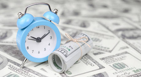 Time management concept. Blue alarm clock lies on a large amount of hundred dollar bills. Time as one of important resources in business