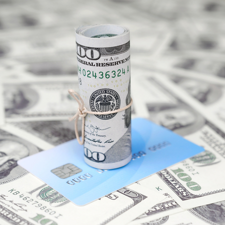 US dollars rolled up and tightened with band lies on credit card. American money and online modern virtual banking concept 版權商用圖片
