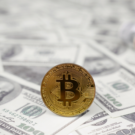 Bitcoin coin and banknotes of one hundred dollar. The concept of reasonable and proper investment of money in cryptocurrency. Earnings in crypto market