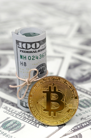 Bitcoin coin and banknotes of one hundred dollar. Conceptual image for global cryptocurrency blockchain payment system
