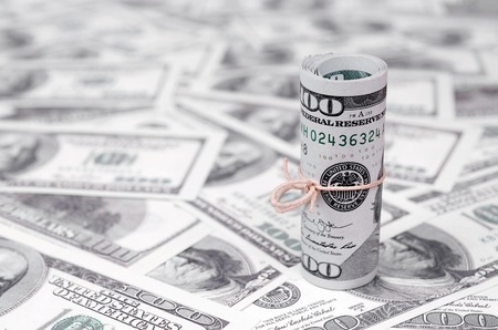 US dollars rolled up and tightened with band lies on a lot of american banknotes with blurred background. Big amount of money