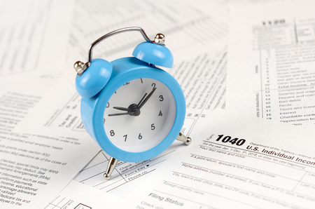 1040 Individual income tax return form with blue alarm clock. Concept of tax period in United States