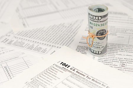 1041 U.S. Income tax return for Estates and Trusts form with roll of american dollar banknotes close up. Concept of tax period in United States