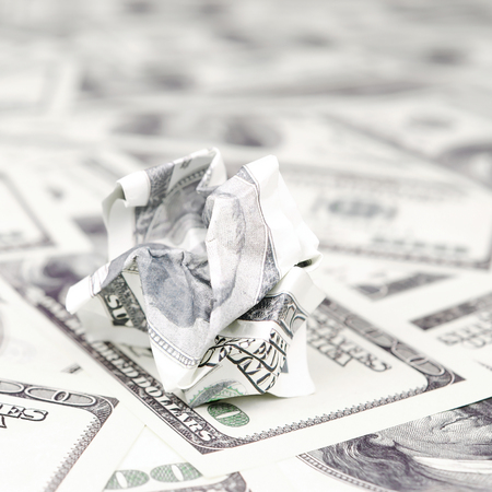 Crumpled dollar bill of the United States lies on the set of smooth money bills. Concept of unreasonable waste of money