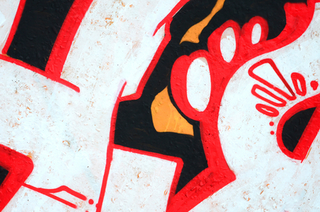 Fragment of colored street art graffiti paintings with contours and shading close up. Background texture of youth contemporary art culture. Orange, red and black colours