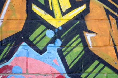 Fragment farbiger Streetart-Graffiti-Gemälde mit Konturen und Schattierungen aus nächster Nähe Hintergrundtextur der Jugend zeitgenössischer Kunstkultur. Gelborange und braune Farben