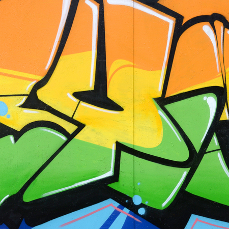 Fragment farbiger Street-Art-Graffiti-Gemälde mit Konturen und Schattierungen aus nächster Nähe. Hintergrundtextur der Jugend zeitgenössischer Kunstkultur. Farben Orange, Gelb und Grün Standard-Bild