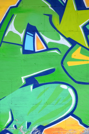 Fragment of colored street art graffiti paintings with contours and shading close up. Background texture of youth contemporary art culture. Green and yellow colours