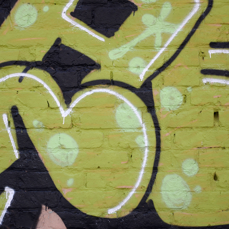 Fragment of colored street art graffiti paintings with contours and shading close up. Background texture of youth contemporary art culture. Green yellow colors