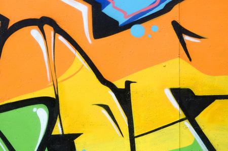 Fragment farbiger Street-Art-Graffiti-Gemälde mit Konturen und Schattierungen aus nächster Nähe. Hintergrundtextur der Jugend zeitgenössischer Kunstkultur. Farben Orange, Gelb und Grün