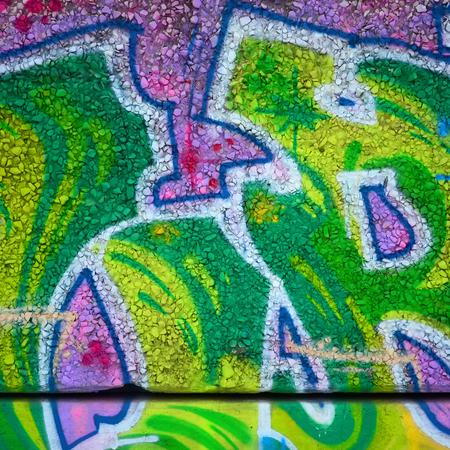 Fragment farbiger Street-Art-Graffiti-Gemälde mit Konturen und Schattierungen aus nächster Nähe. Hintergrundtextur der Jugend zeitgenössischer Kunstkultur. Grüne und gelbe Farben