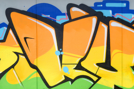 Fragment of colored street art graffiti paintings with contours and shading close up. Background texture of youth contemporary art culture. Orange yellow and green colors