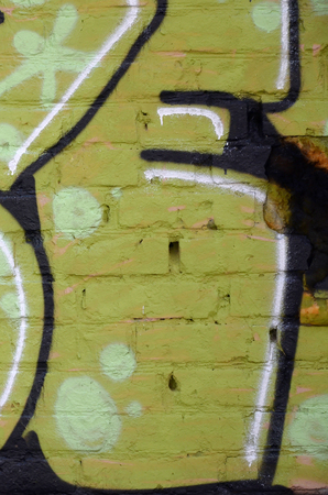 Fragment of colored street art graffiti paintings with contours and shading close up. Background texture of youth contemporary art culture. Green yellow colors 免版税图像