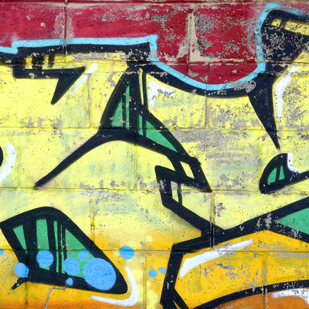 Fragment of colored street art graffiti paintings with contours and shading close up. Background texture of youth contemporary art culture. Yellow orange and brown colors 免版税图像