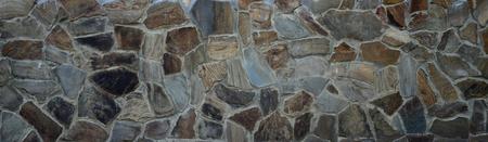 Rustico vecchio mattone beige indossato fondazione con squallide pietre marroni close up texture