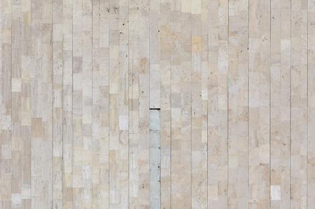 Hintergrundtextur der alten mattbeigen Marmorwand aus einer Vielzahl von großen Fliesen