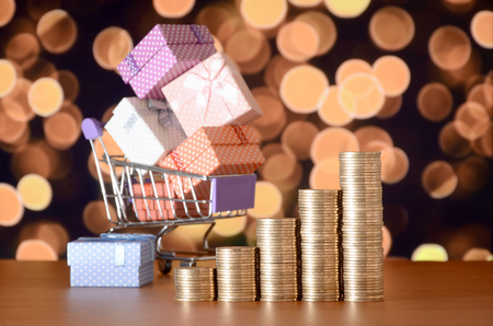 Many gift boxes in shopping cart and golden coin stacks on the colored bokeh background. Shopping and christmas sale concept 写真素材