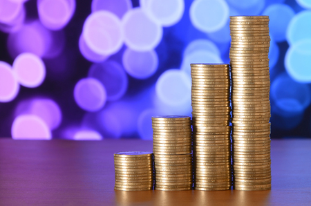 Golden coin stacks arranged as a graph. Increasing columns of coins, step of stacks coin. Business and financial concept idea