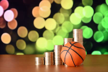 Basketball and stacks of golden coins in growth graph on the blurred bokeh background. Sport betting concept