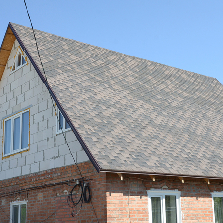 Flexible shingles of bitumen roofing surface on the brick house. Mosaic texture of flat roof tiles with bituminous coating