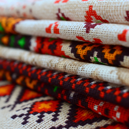 Stack of traditional Ukrainian folk art knitted embroidery patterns on textile fabric. Colored pixel design knitted canvas
