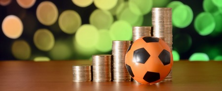 Soccer ball and stacks of golden coins in growth graph on the blurred bokeh background. Sport betting concept