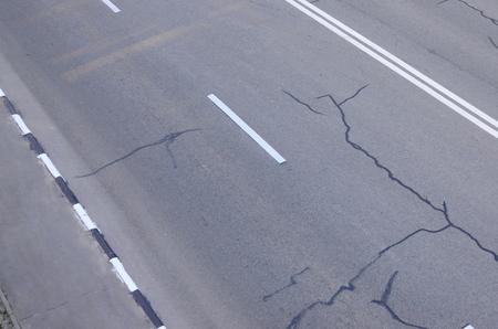 Damaged bad asphalt road with potholes. Patch repair of asphalt. Bad asphalt dangerous broken automobile road, cracks and potholes in asphalt