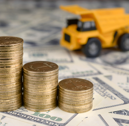 Dump truck toy and stacks of gold coins on background of many hundred dollar bills. Business finance and banking industrial concept idea