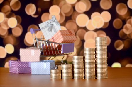 Many gift boxes in shopping cart and golden coin stacks on the colored bokeh background. Shopping and christmas sale concept Reklamní fotografie