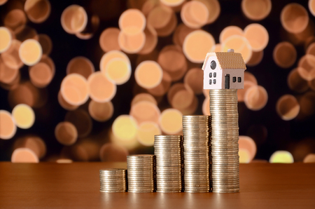Small toy house model and coins stacks in growth graph. Planning savings money of coins to buy a home concept, mortgage and real estate investment