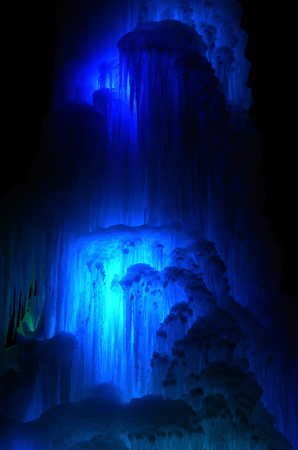 Huge ice icicles. Fragment of large blocks of ice frozen waterfall of water. Blue ice cavern background. Frozen stream waterfall