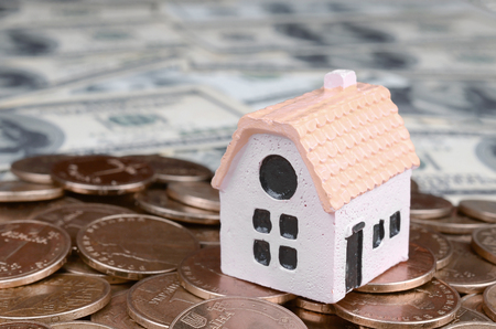 Mini house model on big coins stack on many dollar bills as background. Risk, Assets and Property Investment concept