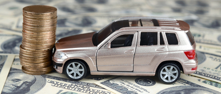 Toy car in accident on a background of 100 dollar bills and stack of golden coins. Car insurance concept Reklamní fotografie
