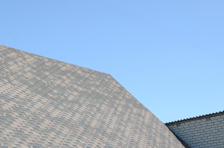 Flexible shingles of bitumen roofing surface on the brick house. Mosaic texture of flat roof tiles with bituminous coating Reklamní fotografie