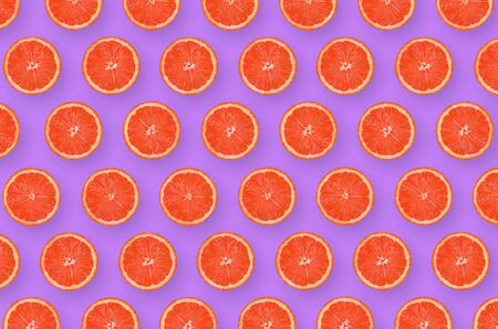 Top view of grapefruit slices on bright purple background. A saturated citrus pattern. Minimalistic flat lay Banco de Imagens