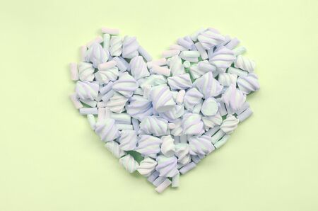 Colorful marshmallow laid out on lime and pink paper background. pastel creative textured heart. minimal. Stock Photo