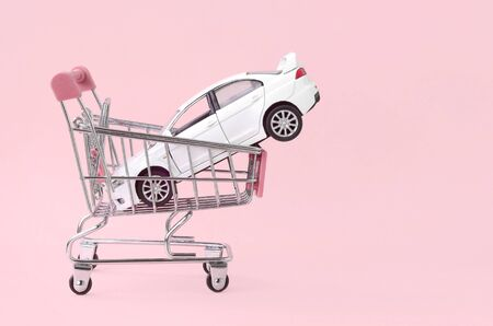 New white toy car in shopping cart as a symbol for car buying and leasing