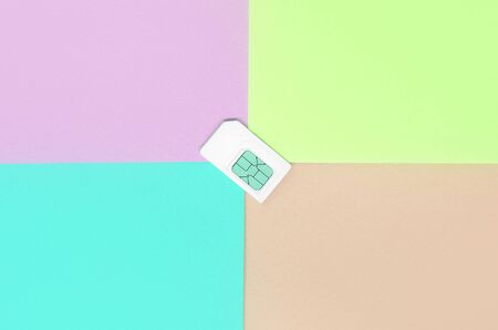 Subscriber identity module. New white SIM card on bright multicolor background. Minimal flat lay top view. Coral pink, lime and blue colors